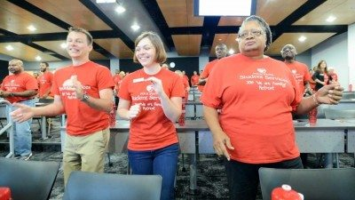"""Polk State Student Services employees, from left, Joshua and Sarah Plazak and Sandra Walker do the """"Eagle Shuffle at the recent Student Services Retreat."""