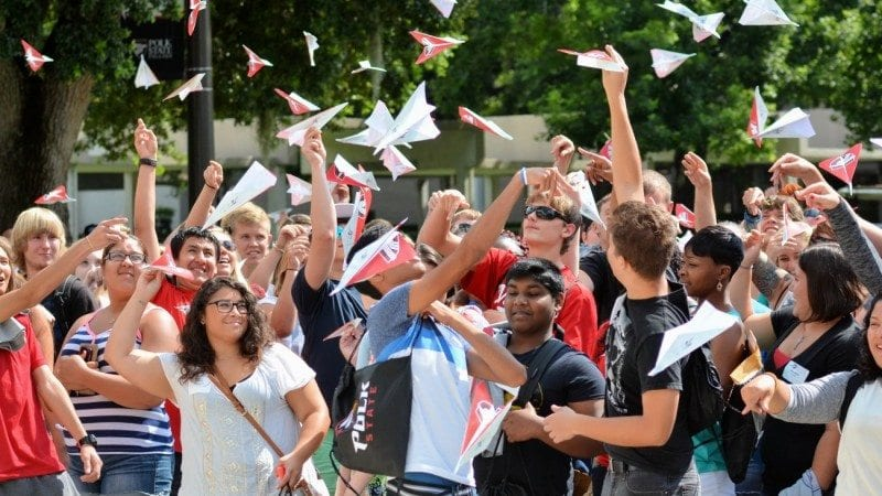 New Polk State freshmen launch their paper airplanes, on which they'd written words of encouragement for one another, at Thursday's First Flight Convocation.
