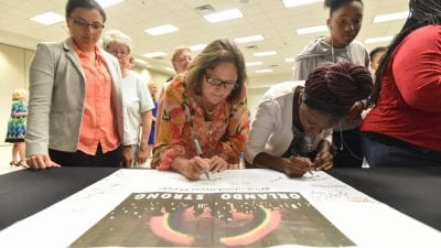 Students and employees sign their names to a banner in support of the Orlando nightclub shooting victims during a memorial event Monday at Polk State Winter Haven.