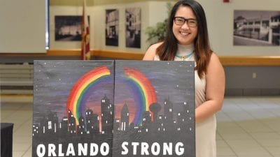 "Polk State alumna Jenny Nguyen with her painting, ""Orlando Strong."""