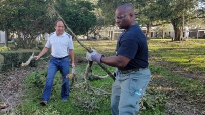 Robbie Manikis, Project Engineer and Lt. Bobby Neil, Security Coordinator, clear tree debris on Winter Haven Campus.