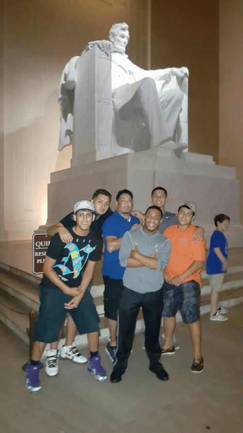 A group of Upward Bound participants enjoy a night tour of the National Mall in Washington, DC, during Discover Summer 2015. Here, several participants and chaperone Jesus Jaime pose at the Lincoln Memorial.