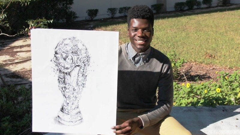 Polk State Chain of Lakes Collegiate High School senior Shedner Agenor with the drawing that will be featured on the cover of the school's 2015-16 yearbook.