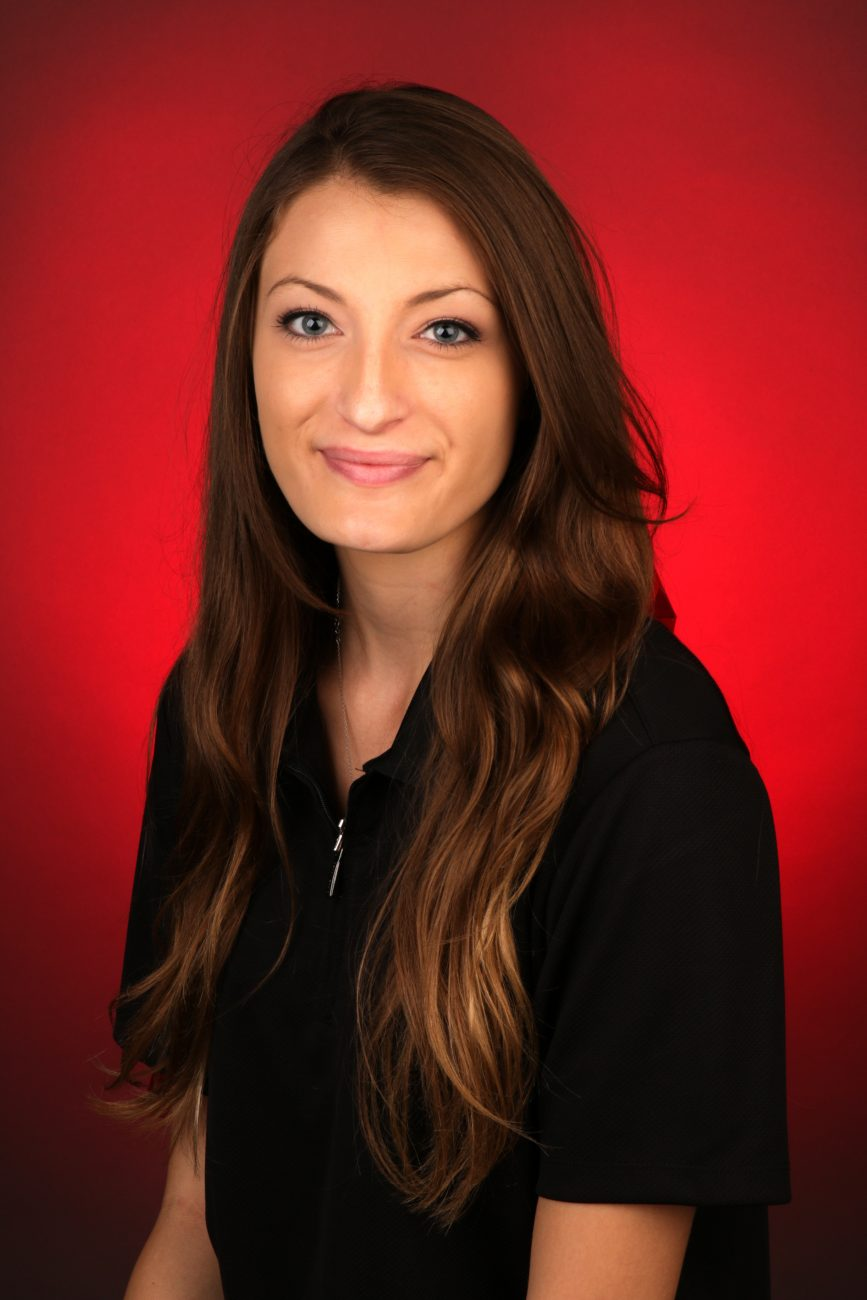 Portrait of Camry Brewer in a black collared shirt against a red backdrop