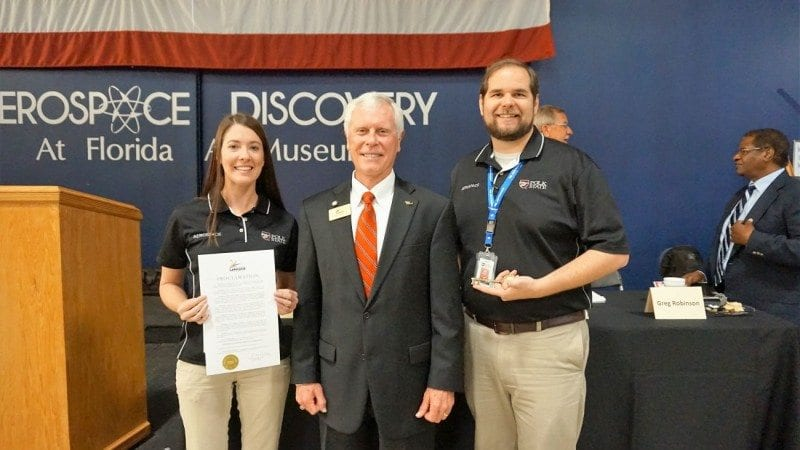 Polk State Aerospace student Karissa Strickland, left, Lakeland Mayor Howard Wiggs, center, and Polk State Aerospace Director Eric Crump. On Tuesday, Wiggs read a proclamation honoring Polk State Aerospace and other local organizations advancing aerospace education in Polk County. Strickland holds a copy of the proclamation. Crump holds an honorary city key.