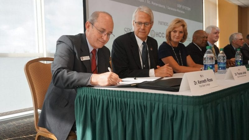 Polk State Vice President for Academic Affairs Kenneth Ross signs the FUSE agreement at USF Tampa on Friday alongside representatives from other FUSE partner institutions.