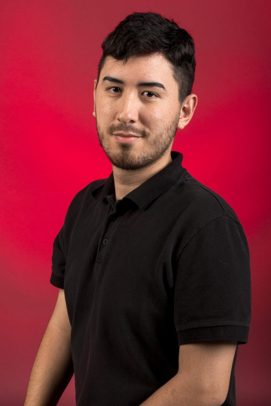 Portrait of Daniel Carrion Jr. in a black collared shirt against a red backdrop