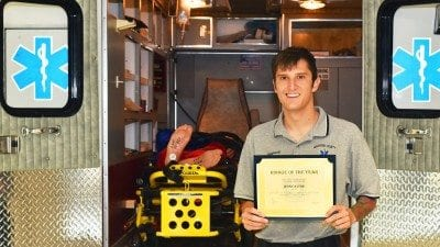 Polk State alumnus Jesse Stine stands with his Rookie of the Year certificate in front of the training ambulance used by Polk State's EMS Program.