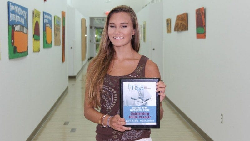 Sydney Weber displays the Outstanding HOSA Chapter award Polk State Chain of Lakes Collegiate received at HOSA's national competition in late June.