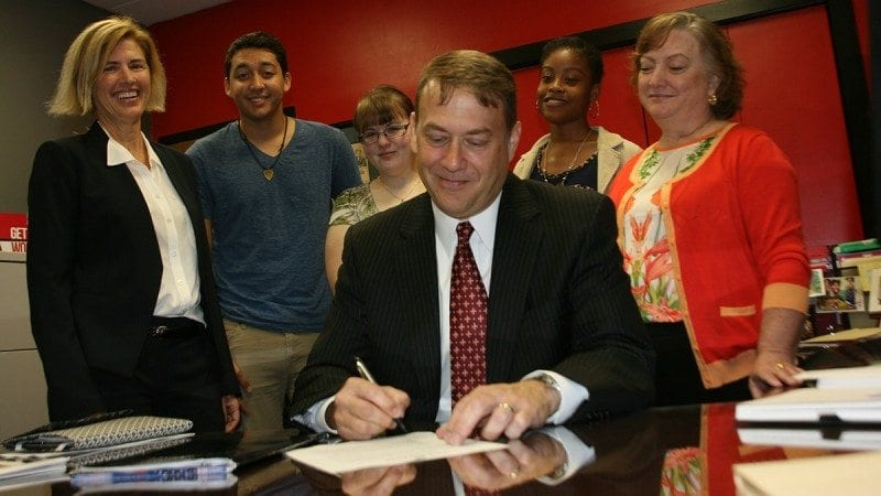 Winter Haven Economic Development Council Executive Director Bruce Lyon signs an agreement with Polk State that calls for increased collaboration on initiatives including internships, events and mentorships for students. Looking on are Julie Sands (L), program manager for the WHEDC, Bachelor of Applied Science Program Director Maria Lehcozky (R), and several students who attend Polk State Winter Haven.