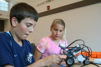 Seventh-graders Winston Allen and Grace Borst make adjustments to their robot.