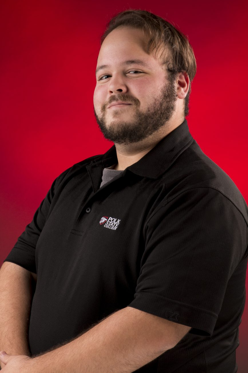 Portrait of Juan Santana in a black collared Polk State College shirt against a red backdrop