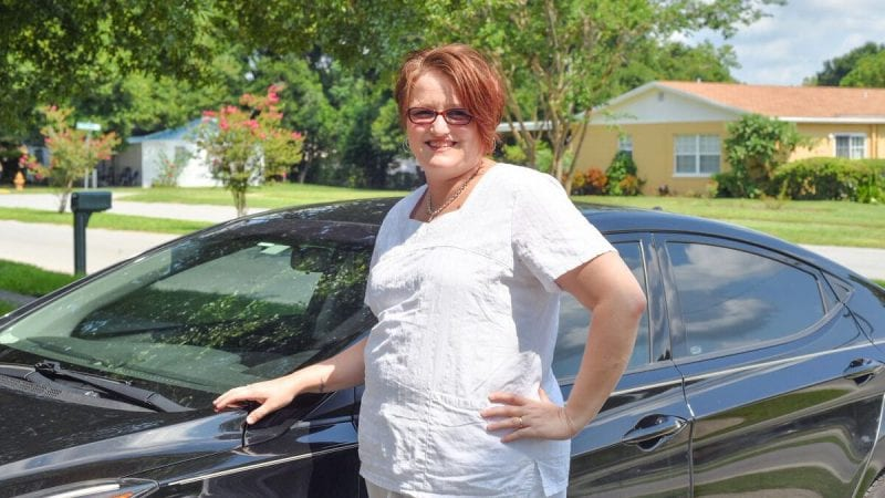Polk State alumna Amy Eaton stands next to the new car she was able to purchase after graduating from Polk State free of student-loan debt.
