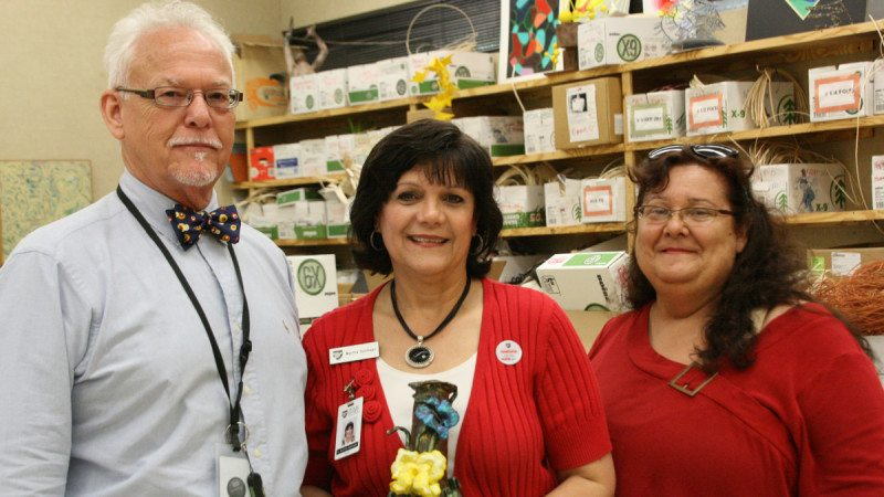 From left, Polk State Art Professor Gary Baker, Dean of Academic Affairs Martha Santiago, and student Laura Hawkins. Hawkins has multiple vision impairments but still pursues her interest in art. She recently presented Santiago with a vase she made in Baker's class.