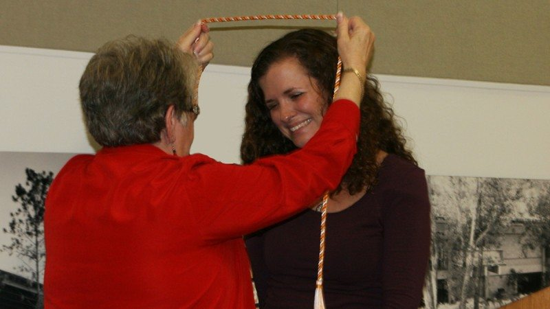 Polk State Nursing Director Annette Hutcherson places a cord around the neck of student Alison Richards, a symbol of her induction into Alpha Delta Nu, the national honor society of associate-degree-level nurses. The College held its first induction ceremony for its chapter of Alpha Delta Nu on Monday. Sen. Denise Grimsley, an alumna of the Nursing program, spoke at the ceremony.
