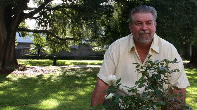 Polk State Athletic Director Bing Tyus is also a successful gardener. Here, he shows off two rose bushes he grew from clippings off other bushes in his yard.