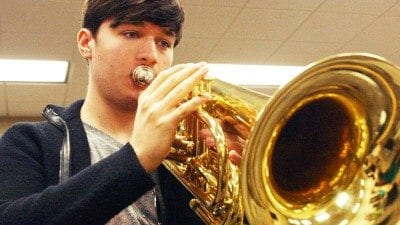 Polk State Chain of Lakes Collegiate High School student Andrew Sallee practices the baritone, the instrument he will play in this year's Macy's Thanksgiving Day Parade.