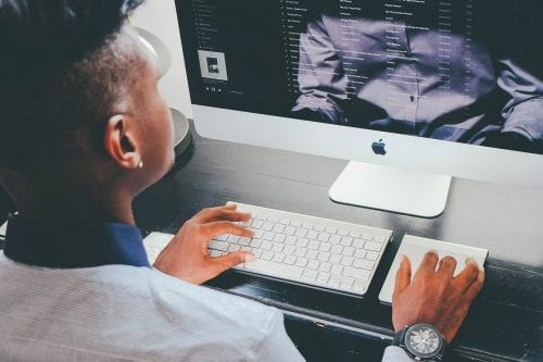 Young African-American male browsing the web on a iMac computer.