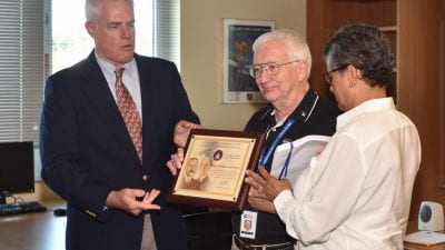 Polk State Aerospace Program Coordinator Mike Courtney, center, receives the FAA's Wright Brothers Master Pilot Award from the FAA's Robert Jex with his wife Doris by his side.