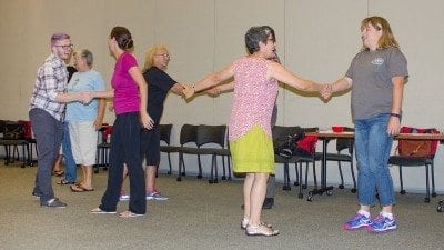 Ilene Fins, second from right, one of the instructors in the Arts Integration Summer Institute, leads teachers in a group handshake, one of the exercises that can be used to get students moving, interacting and excited at the start of the day.