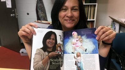 Polk State student Patty Rowe holds the October 2016 edition of Dolls magazine, which includes a feature on her and her work.