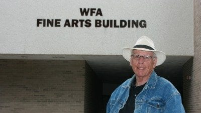 "Norm Small, Polk's first theatre director, outside the Winter Haven Fine Arts Building. Small staged the first play in the Fine Arts Theatre, ""Pippin,"" in the 1970s."