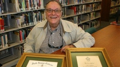Carl Caldwell graduated from what was then Polk Junior College in 1967. He went on to have a career in accounting. He is shown here at the Dundee Public Library, where he spends much of his time, with his diploma and certificate of induction into Polk's Xi Pi chapter of Phi Theta Kappa.