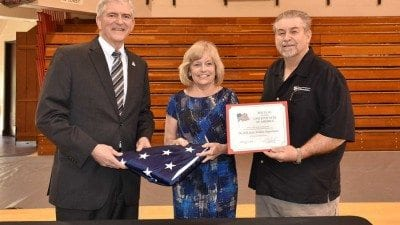 Rep. Daniel Webster (L) presents a flag that was flown over the U.S. Capitol to Polk State President Eileen Holden and Athletic Director Bing Tyus. The flag will be displayed in the Polk State Winter Haven Health Center.