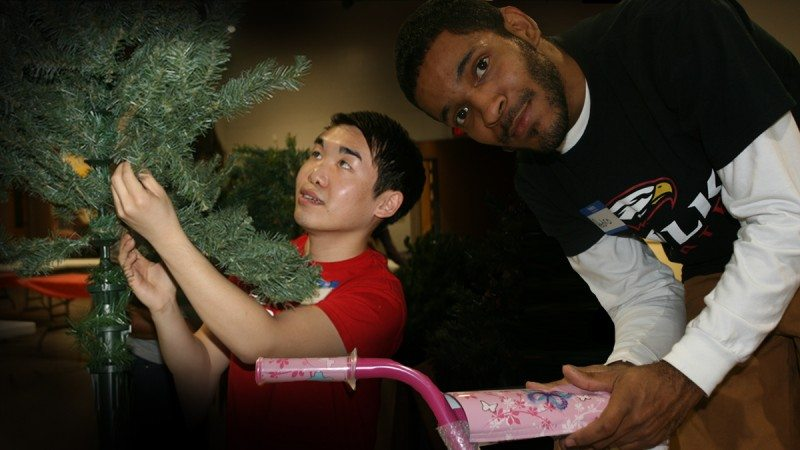 Chris Ly (L) and Pedro Martinez were among a dozen or so Polk State Lakeland students who volunteered at Parker Street Ministries to assemble the annual Christmas Store.