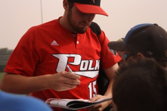 Polk State Pitcher Alec Asher signs autographs after the Eagles win in the first round of the NJCAA JuCo World Series.