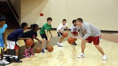 Polk State Assistant Basketball Coach Stephen Perkins instructs kids in the College's summer basketball camp.