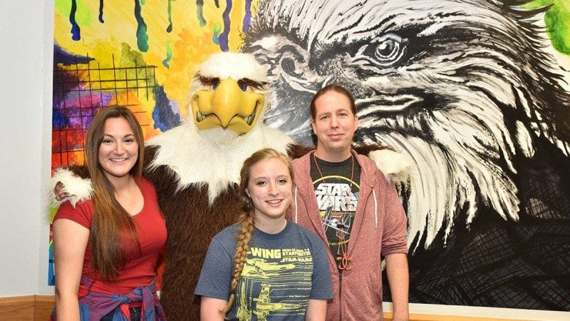 Amanda Frazier, left, designed the new mural in the Polk State Winter Haven game room. Her classmates, Kayla Wasmund, center, and Scott Whitley, right, helped paint it on the wall. On hand for Wednesday's mural reveal was Charlie, Polk State's mascot.