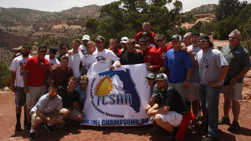 Polk State Baseball players, coaches and others traveling with them in Grand Junction, Colo., display the team's state championship banner at Colorado National Monument on Friday.