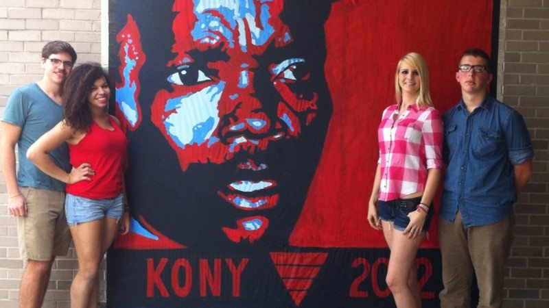 Polk State Visual Arts Society members recently displayed their latest mural, depicting Ugandan war criminal Jospeh Kony. From left are Brayden Hooper, Gaby Conliffe, Alexandria Trsek and Jordan Neumann, all of whom helped paint the mural. Not pictured is Amanda Finch. The students all gave credit to Art Professor Vilas Tonape for his support of the project.