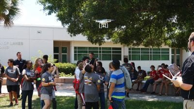 Participants in Polk State College's TALON Robotics program watch as a drone whizzes over their heads during a presentation on Friday. Polk State Aerospace Program Director Eric Crump, far right, gave the drone presentation.