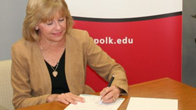 Polk State President Eileen Holden adds her signature to the Graduate Polk initiative, a Polk Vision education initiative to help area residents complete their college degrees.