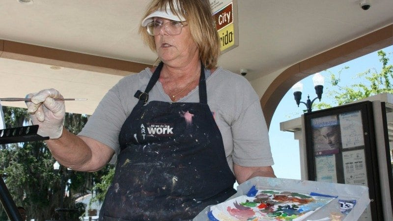 Polk State student Joyce Irwin paints at the Winter Haven bus terminal on Monday as part of Polk Vision's Art In Transit.