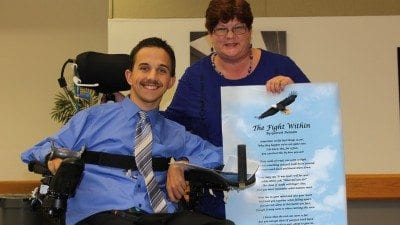 "Garrett Putnam with Mary Westgate, Polk State's disability services coordinator. Westgate presented Putnam with a laminated version of his poem, ""The Fight Within,"" during last month's Criminal Justice Teach-In."