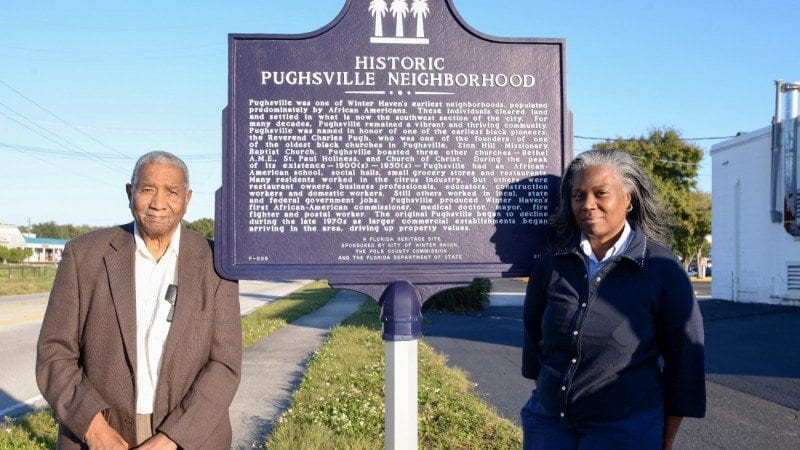 Lemuel Geathers and Patricia Smith-Fields, natives of Pughsville, stand near a historical marker for their neighborhood. The rezoning of Pughsville in the 1960s helped bring Polk State to Winter Haven.