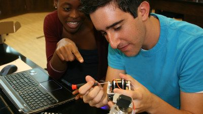 Polk State Chain of Lakes Collegiate High School students and Scholarobotics Academy participants Natalie Weekfell (L) and Randy Esfahani make adjustments to a robotic arm that will be used for microsuturing.
