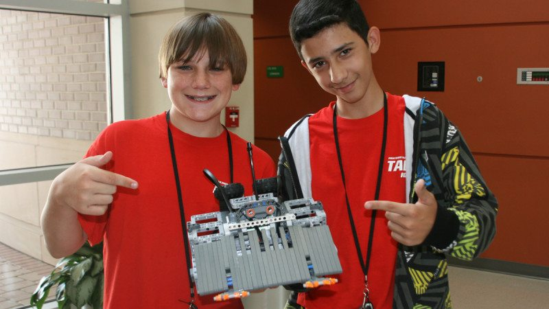 Carson Warner (L) and Michael Jenkins won first place in the sumo competition at Thursday's Robot Rumble. Warner and Jenkins said adding claws to the front of their machine was key to securing the victory.